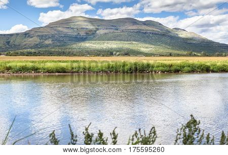 Rural pond with reflections from dappled sun through cloud sky - South African farm pond with hills and grass field