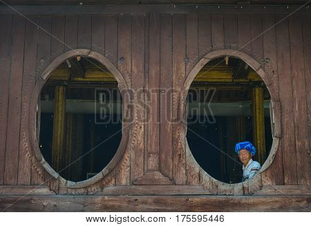 Burmese Man Sitting At The Wooden House