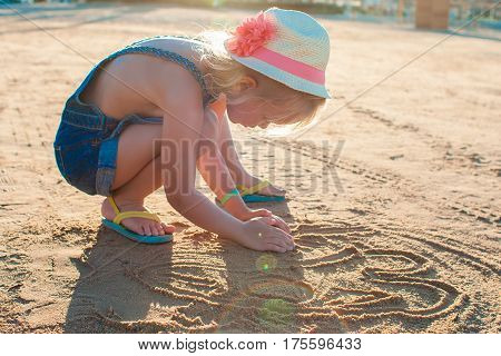 Cute little girl playing with sand on the beach. Active summer vacation.