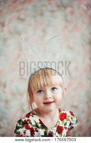 Portrait of a cute happy little girl with bunny ears. Easter portrait. Floral background.