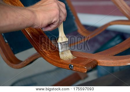 Hand with a brush paints with a varnish a old chair armrest