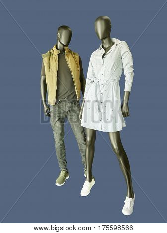 Two mannequins male and female dressed in casual clothes isolated on gray background. No brand names or copyright objects.