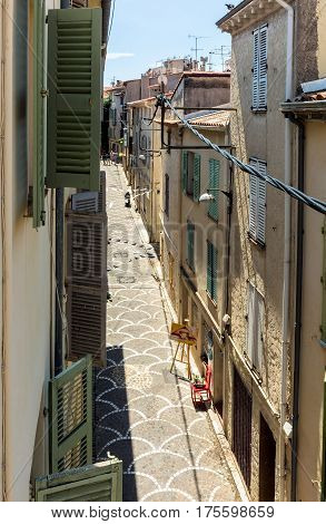 Antibes France - June 27 2016: day view of old town street with tourists in Antibes France.