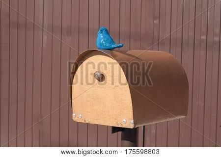 mailbox decorated with blue bird against brown fence