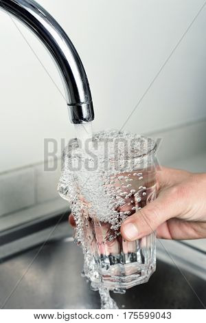 closeup of a young caucasian man filling a glass of tap water