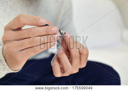 closeup of a young caucasian man cutting his fingernails with a nail clipper
