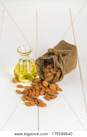 Bottle Of Almond Oil And Almonds On White Wooden Background.