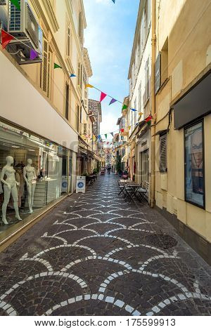 Antibes, France - June 27, 2016: day view of Rue Fourmilliere with shops in Antibes France. Antibes is a popular seaside town in the heart of the Cote d'Azur.