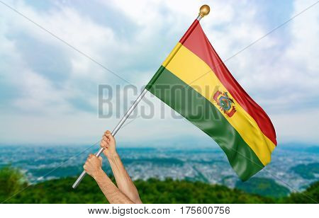 Young man's hands proudly waving the Bolivia national flag in the sky, part 3D rendering