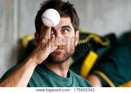 SCOTTSDALE, AZ-MAR 6: Oakland Athletics catcher John Jaso rolls a baseball on his fingers in the dugout at Salt River Fields at Talking Stick on March 6, 2014 in Scottsdale, Arizona.