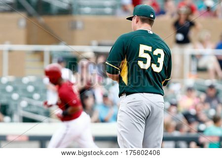 SCOTTSDALE, AZ-MAR 6: Oakland Athletics shortstop Addison Russell runs past Oakland Athletics pitcher Jeremy McBryde at Salt River Fields at Talking Stick on March 6, 2014 in Scottsdale, Arizona.