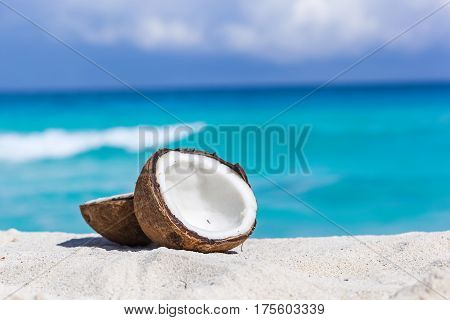 Broken Brown Coconut On Sandy Beach