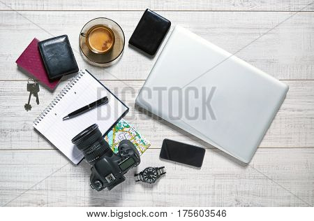 View of a wooden table with a laptop, external hdd, mobile, notebook, camera, pen, watch, wallet, passport, map, keys and a cup of coffee on it