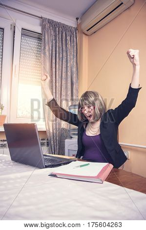 Young corporate businesswoman cheering victoriously, received gr