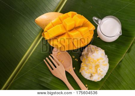 thailand dessert by sweet mango and sticky rice on banana leaf