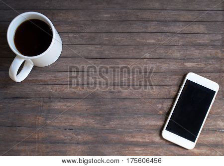 White coffee mug and white smartphone on warm rustic wood table. Black screen smartphone on empty background. Coffee and phone with blank text banner place. Vintage cafe flat lay composition template
