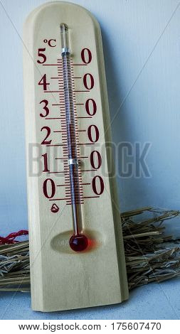Wooden thermometer is light on the windowsill