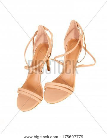 A pair of beige woman's sandals with high heels sitting isolated for white background.