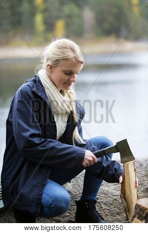 Woman Cutting Wood For Bonfire On Lakeside Camping