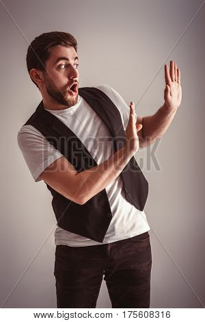 cute young frightened man with a beard in a white shirt and a black waistcoat over gray background