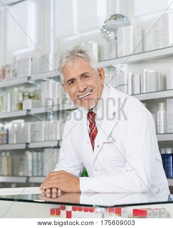 Confident Pharmacist Smiling While Leaning On Counter