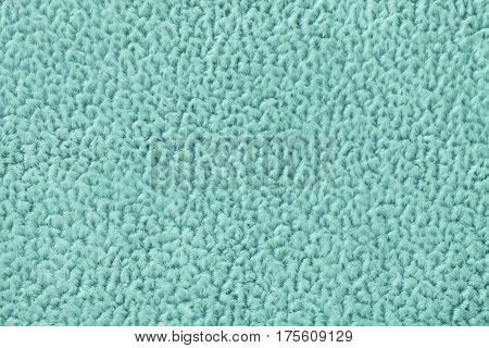 Light turquoise fluffy background of soft fleecy cloth. Texture of textile closeup.