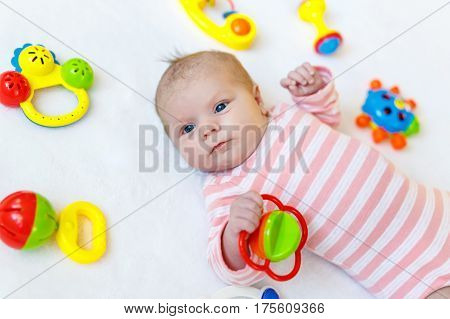 Cute adorable newborn baby playing with lots of colorful rattle toys on white background. New born child, little girl looking surprised at the camera. Family, new life, childhood, beginning concept