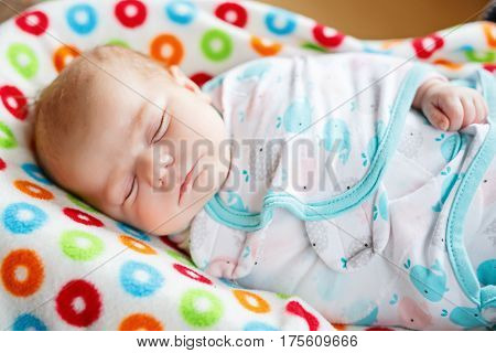 Cute adorable newborn baby wrapped in colorful blanket, sleeping and dreaming. Closeup of peaceful child, little baby girl . Family, Birth, new life. Swaddling as method for calm child