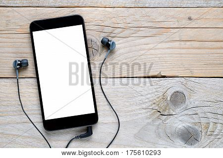 Smartphone with earphones on old wooden table