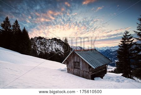 wooden alpine hut in winter mountains Germany