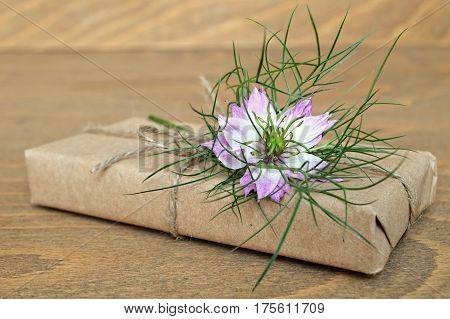 Parcel  wrapped in brown paper and nigella flower