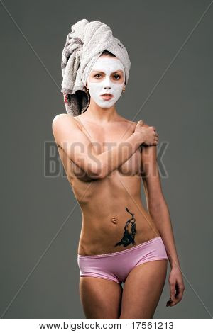Healthy topless girl with facial mask and towel over head