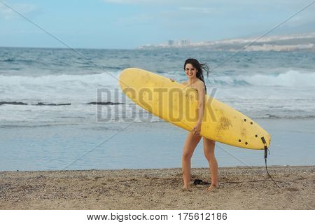 Pretty happy girl surfer or beautiful woman sexy slim brunette in sexi swimsuit with yellow surfboard on sandy beach outdoors on sunny summer day on blue sea background