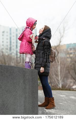 Happy young mother and child daughter kissing on strolling spring city park