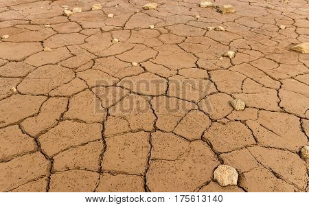 Clay texture of drying prism desiccation cracks in ground. Cracked and dried mud dirt and stones background texture.