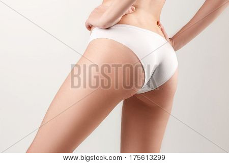 Checking cellulite. Young, slim, healthy and beautiful woman isolated on the white background. The hip of girl closeup