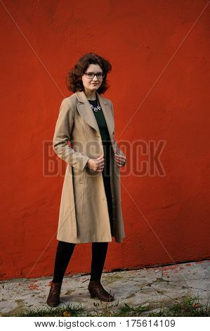 Slender brunette girl in beige coat with spectacles at red wall with copy space