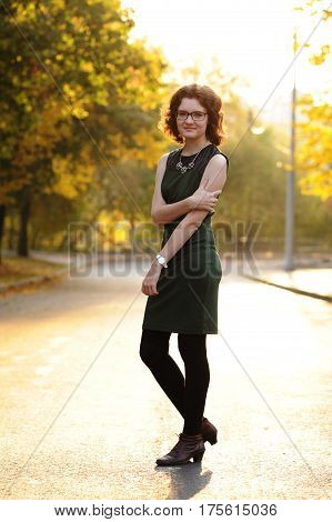 Slender brunette girl in green dress with spectacles in empty street at sunrise vertical