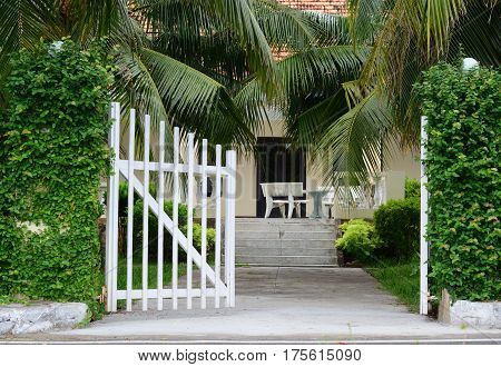 White Picket Fence With Green Trees At Sunny Day
