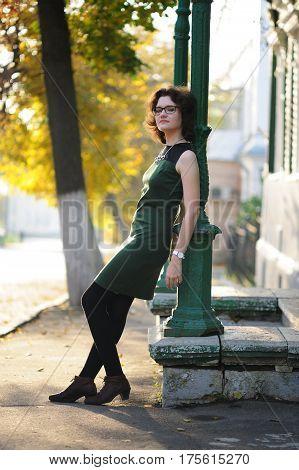Slender brunette girl in green dress with spectacles by column at sunrise vertical