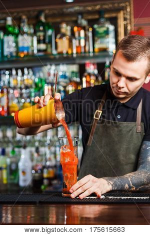 The bartender making cocktail Bloody Mary in a nightclub bar. Pouring cocktail into highball.