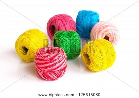 Multicolored skeins of yarn are randomly scattered on the surface.