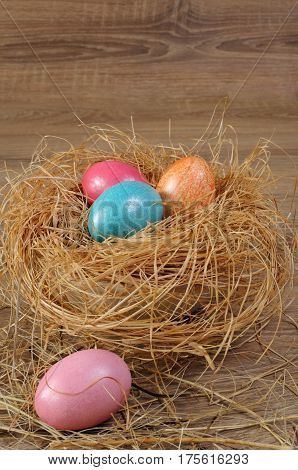 Decorations for Easter. Colored chicken eggs in a nest of hay on a wooden background