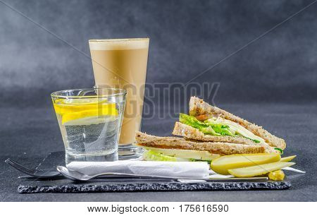 set consisting of two sandwiches malted bread with vintage cheddar cheese pickles red onion tomato lettuce water and coffee latte breakfast set