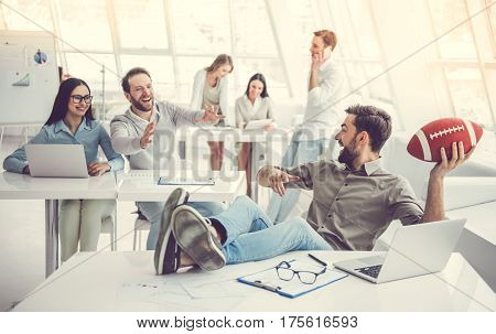 Business people are using gadgets talking playing with ball and smiling while working in office