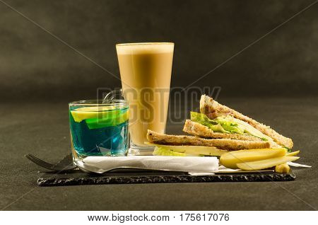 set consisting of two sandwiches malted bread with vintage cheddar cheese pickles red onion tomato lettuce blue drink and coffee latte breakfast set