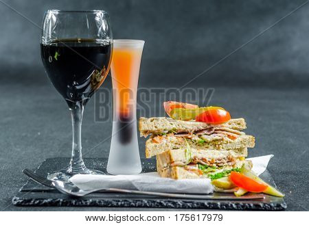Two sandwiches malted bread with smoke flavor bacon pickles mayonnaise tomato lettuce drink with red wine, tasty set