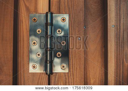 Metallic hinge on wooden door closeup view