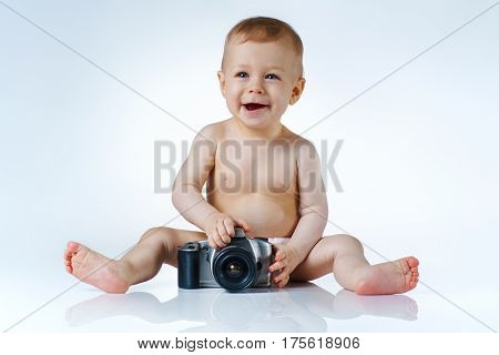 Eight month baby trying to be photographer and playing with camera on white background with reflection