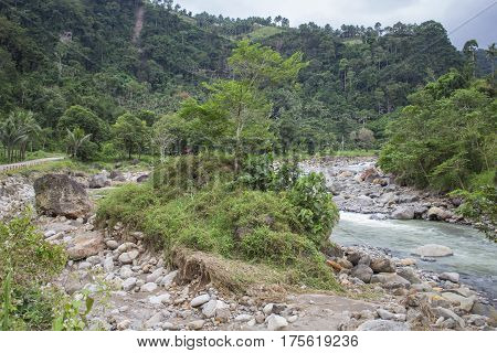 Tropical landscape with small river in stone riverbed and forest hills. Rocky riverbed with small island. Tropic greenery in rainy season. Jungle bush and trees in river valley between mountains.